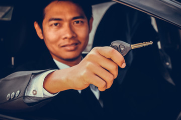Business man showing key and sit in car