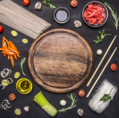raw buckwheat noodles with vegetables, ginger, chopsticks and ingredients, laid out around the cutting board place for text,frame on wooden rustic background top view close up