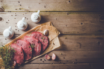 Raw beef steak on wooden table