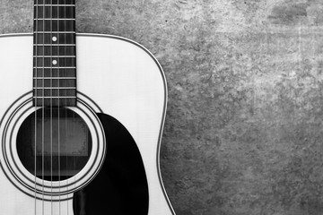 acoustic guitar on the background of a concrete wall close-up, monochrome