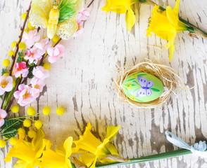 spring floral decoration and easter egg inside straw nest