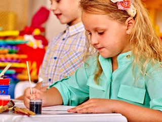 Group kids keeps brush painting on table in  kindergarten .