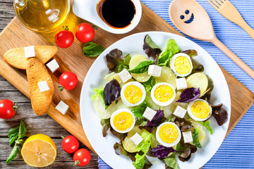 potato salad with chicken eggs, leaves oakleaf lettuce, cheese,