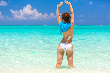 Young woman in bikini standing in the water on beautiful maldivian beach