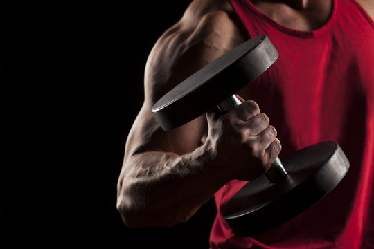muscular man in red shirt posing with weights