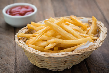 French fries in basket and ketchup on wooden table