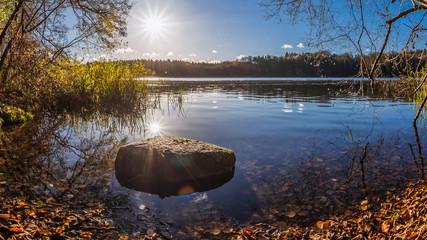 Im Wasser liegender Stein in der Morgensonne am Hellsee