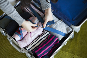 Women are stuffed with clothes side by side in the suitcase