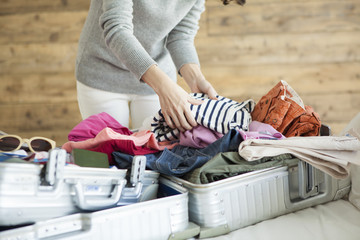 Women are stuffed with clothes in suitcase