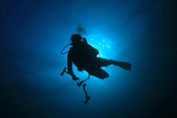 Scuba diver silhouette against sun