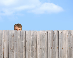 A goofy, happy man is being a peeping tom and nosy neighbour by stalking, watching and gawking over a wooden privacy fence