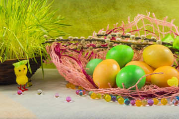 Easter colored eggs and willow on a table, selective focus