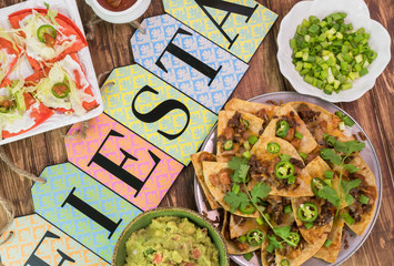 Mexican fiesta table with nachos, tortilla chips, quesadillas, guacamole.
