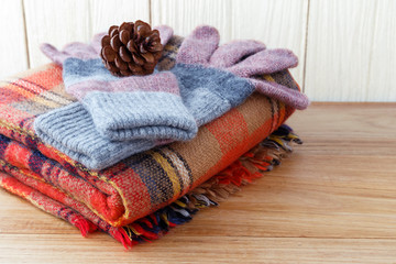 Winter fashion clothing with scarft gloves and blanket with wood background