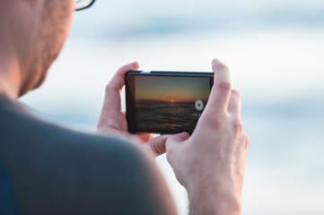 スマートフォンで夕日を撮影する男性