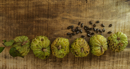 Ripe Sugar-apple Seeds by Unbroken Fruits on Wooden Table