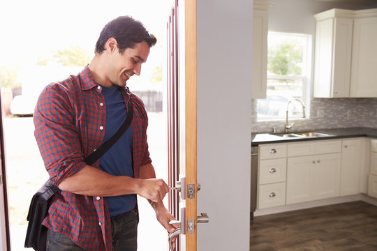 Man Coming Home From Work And Opening Door Of Apartment