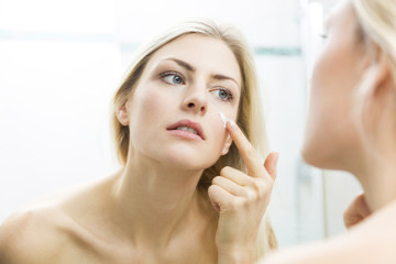 Pretty young woman applying a cream to her face