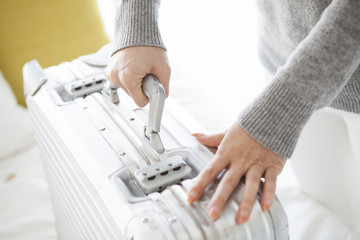 Woman is trying to lift the suitcase