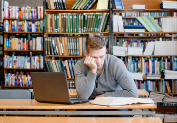 sad and tired male student n library