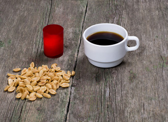 coffee, peanut and red candle, on a wooden table
