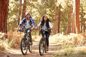 Fototapeten Radsport African American Couple Cycling Through Fall Woodland