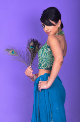Asian model wearing indian dress and peacock feather on violet background at studio shoot