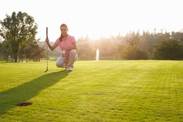 Female Golfer Lining Up Putt On Green