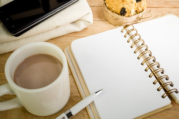 Blank notebook with coffee  on wood background