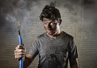 young man holding cable smoking after electrical accident with dirty burnt face in funny sad expression
