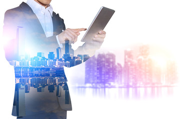 Double exposure of businessman holding tablet with cityscape blu