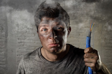 young man holding electrical cable smoking after electrical accident with dirty burnt face in funny sad expression