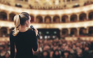 Donna con microfono su palco teatro canta