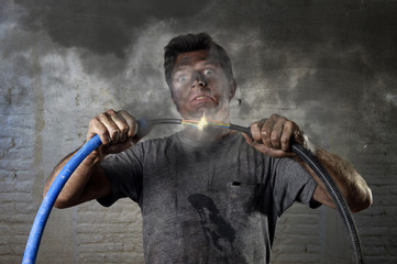 untrained man joining cable suffering electrical accident with dirty burnt face shock expression