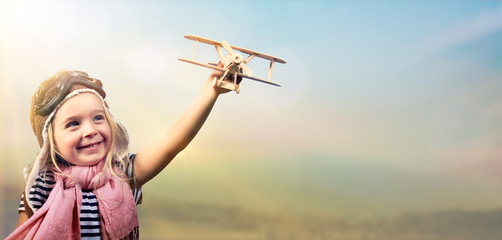 Fotobehang - Freedom To Dream - Joyful Child Playing With Airplane Against The Sky