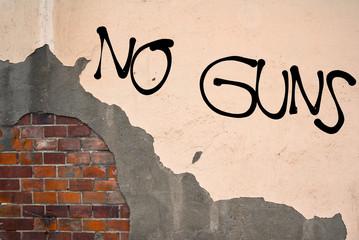 Handwritten graffiti No Guns sprayed on the wall, anarchist aesthetics