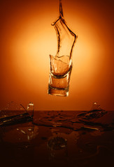 Exploding Glass cup with water shattering over orange background.