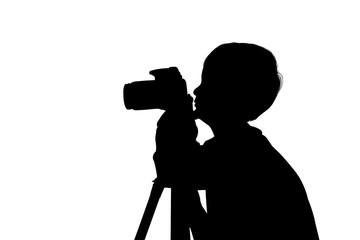 silhouette of cute little boy taking camera