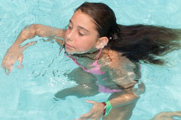 Top view of young  girl in the swimming pool