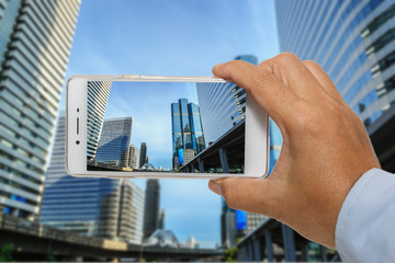 Men Hand holding a smart phone photography Building in Bangkok,C