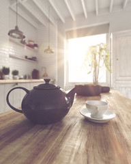 Fat tea pot beside cup with saucer on table