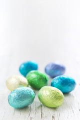 Small chocolate Easter eggs on a rustic white background