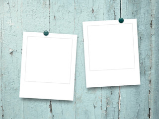 Close-up of two square photo frames with pins on aqua wooden background