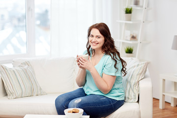 happy plus size woman with cup and cookies at home