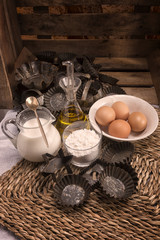 ingredients for muffins and cakes, traditionally , molds , wooden box , milk, eggs , olive oil and flour with traditional molds for craftsmanship