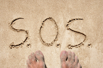 Concept or conceptual S.O.S. text handwritten in sand on a beach in an exotic island background