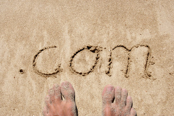 The word .com handwritten in sand on a beach, ideal for internet or conceptual designs background