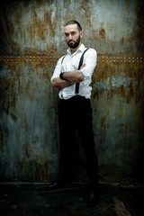 Handsome man posing in white shirt on dark metal wall background