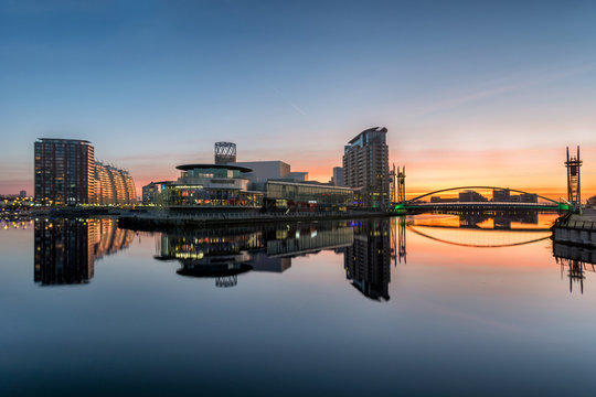 Orange sunrise at Salford Quays with blue sky and clear reflections in canal.