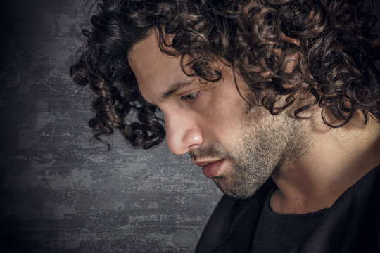 Portrait of desperate young attractive man with curly hair